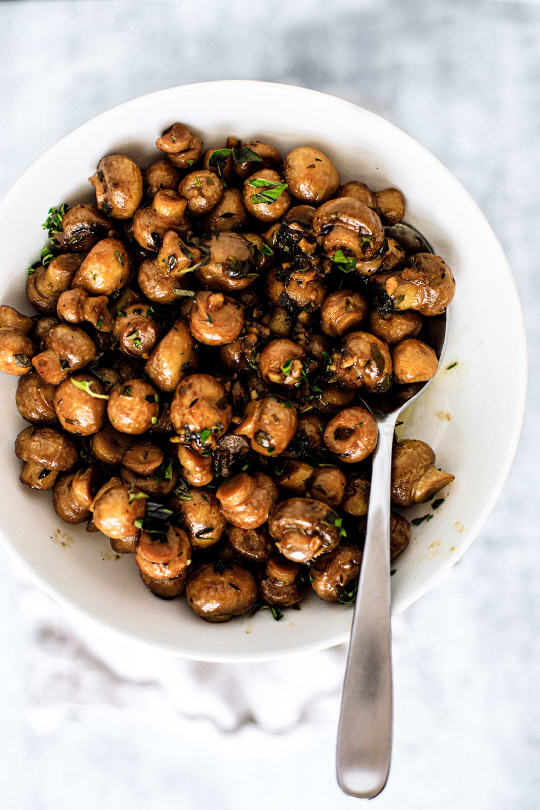 Serving bowl full of beer butter mushrooms garnished with fresh herbs.