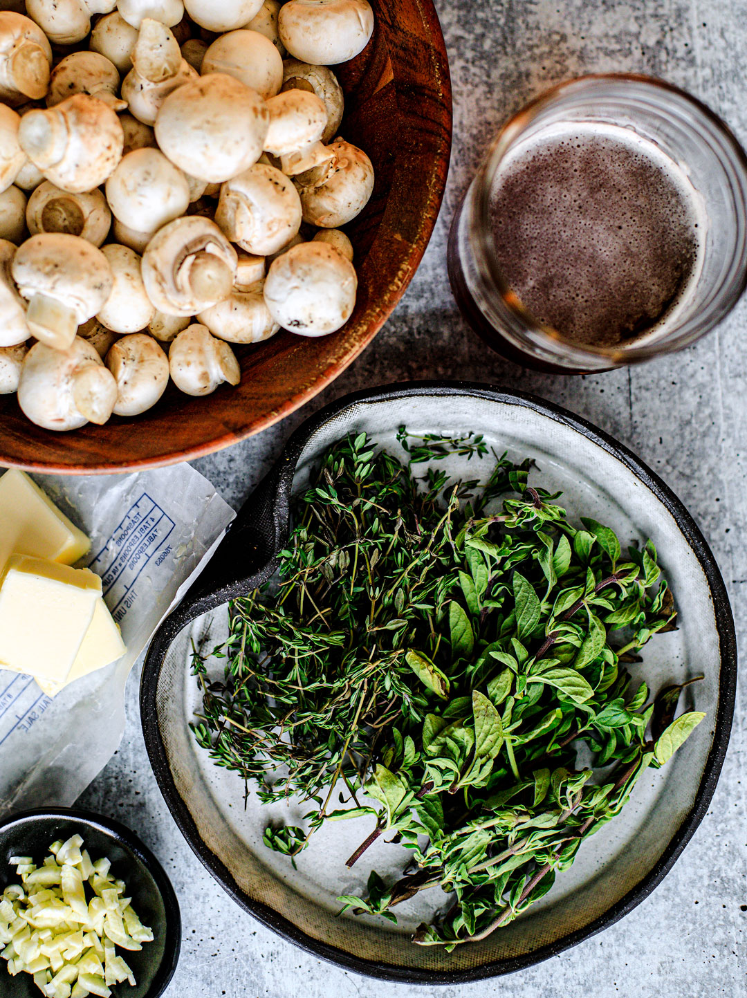 Tablescape of ingredients including a bowl of button mushrooms, a plate full of fresh herbs, a glass of beer, pats of butter, and a pinch bowl of minced garlic.