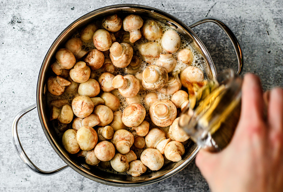 Pan of button mushrooms with beer being poured over top of them.