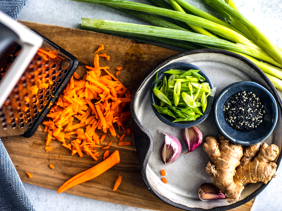 Cutting board with shredded carrots, scallions, garlic cloves, ginger root, and pinch bowl of sesame seeds.