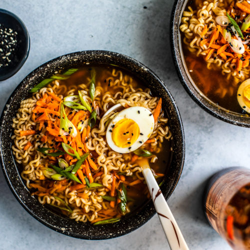 Ramen bowl with soft-boiled egg and a pinch bowl of sesame seeds.