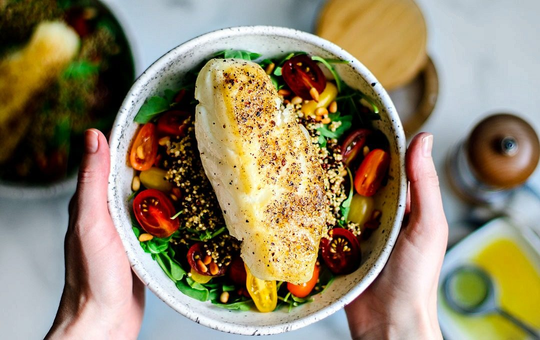 Hands holding up bowl of salad topped with sea bass.