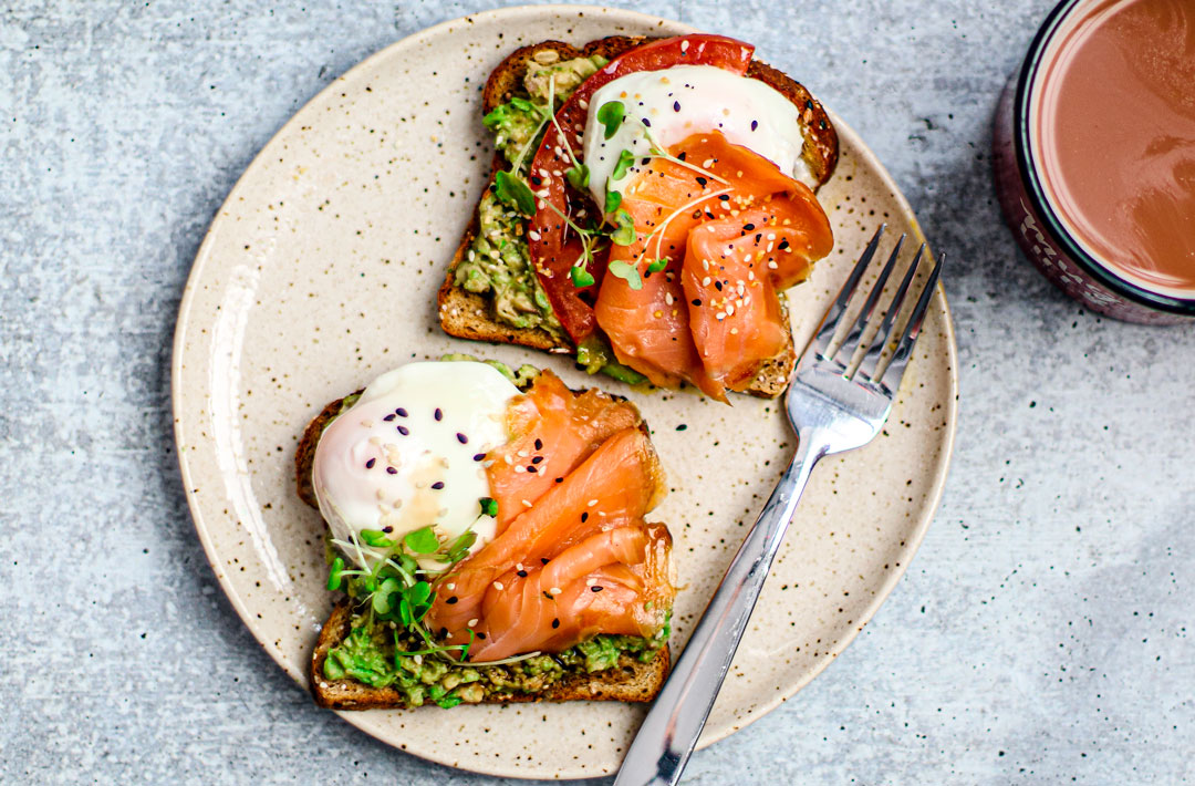Slices of toast on a plate with smoked salmon, avocado, and poached eggs.