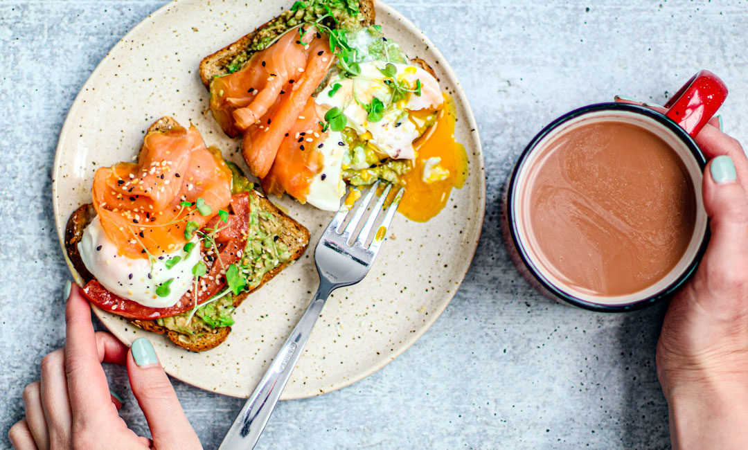 Slices of toast on a plate with smoked salmon, avocado, and poached eggs with leaky yokes.