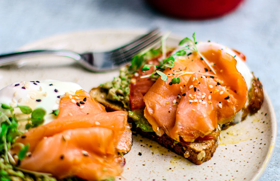 Close up of smoked salmon and poached eggs on toast with avocado.