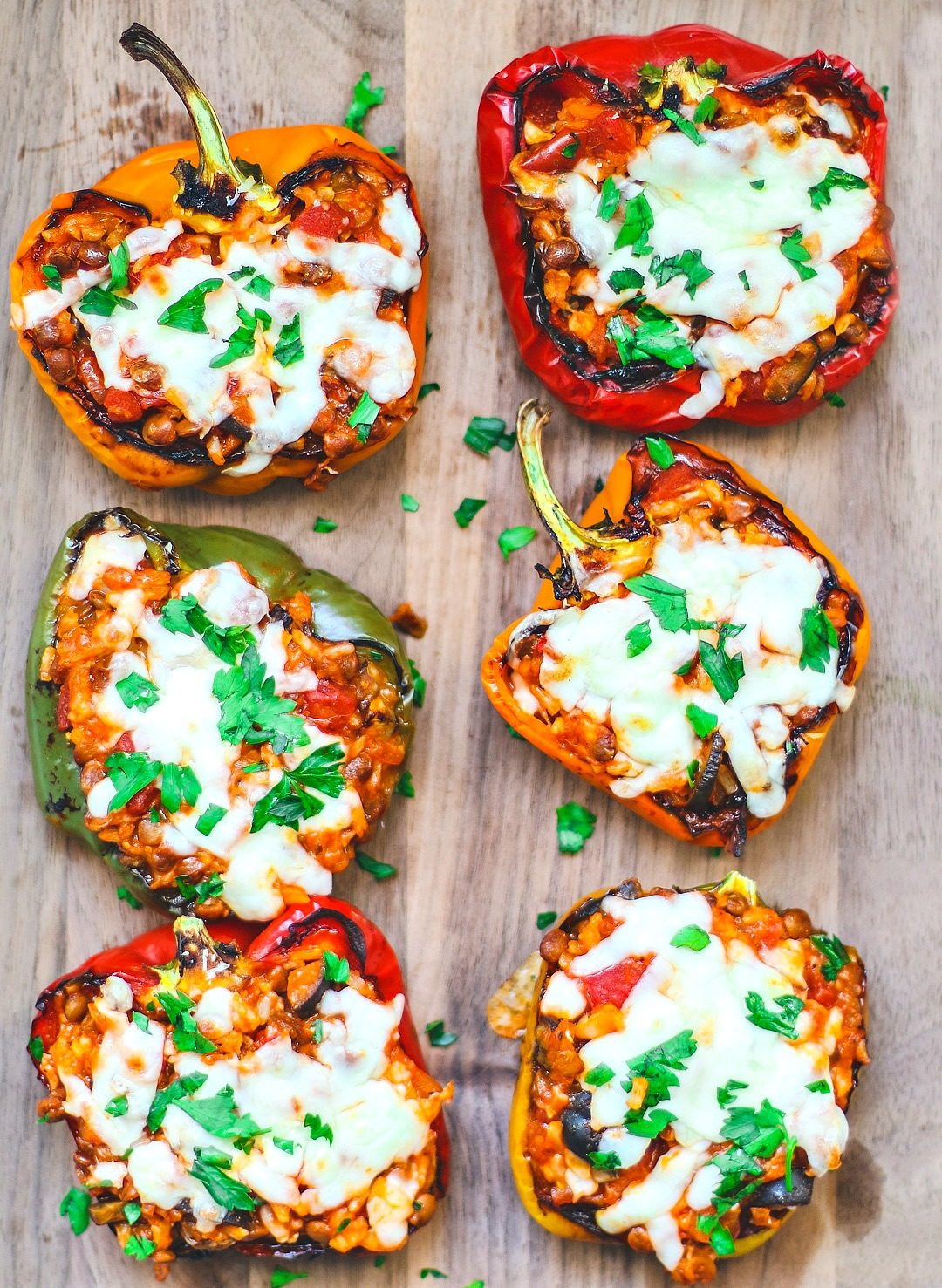 Stuffed peppers on a platter covered in cheese.