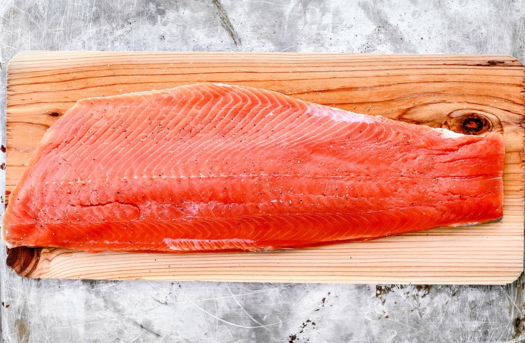 Cedar plank with large salmon fillet on it.