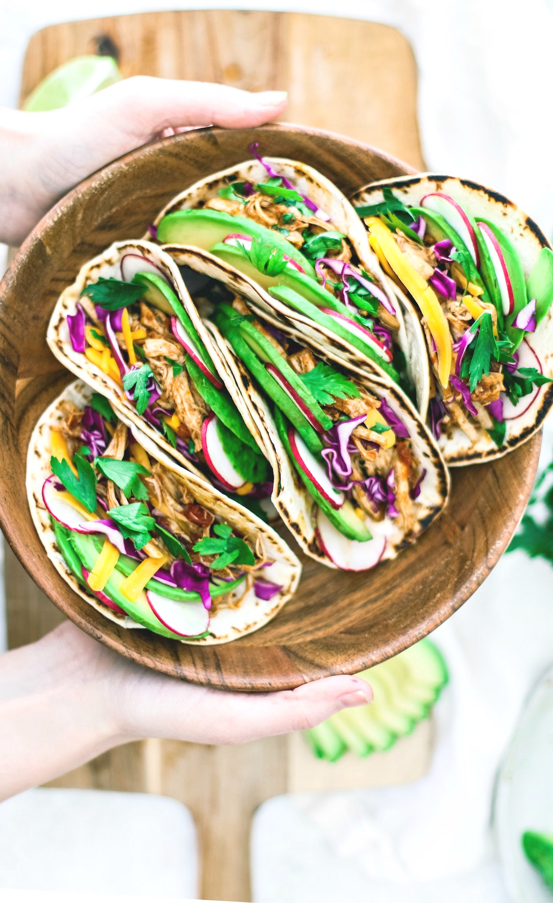 Hands holding bowl of colorful tacos.