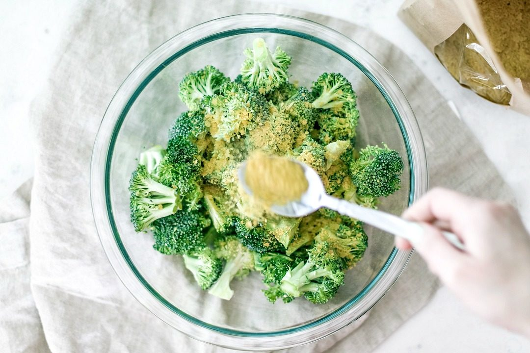 Hand sprinkling nutritional yeast over broccoli in a bowl