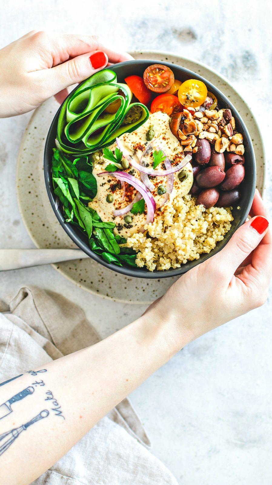 Hands holding bowl of Mediterranean Quinoa Salad