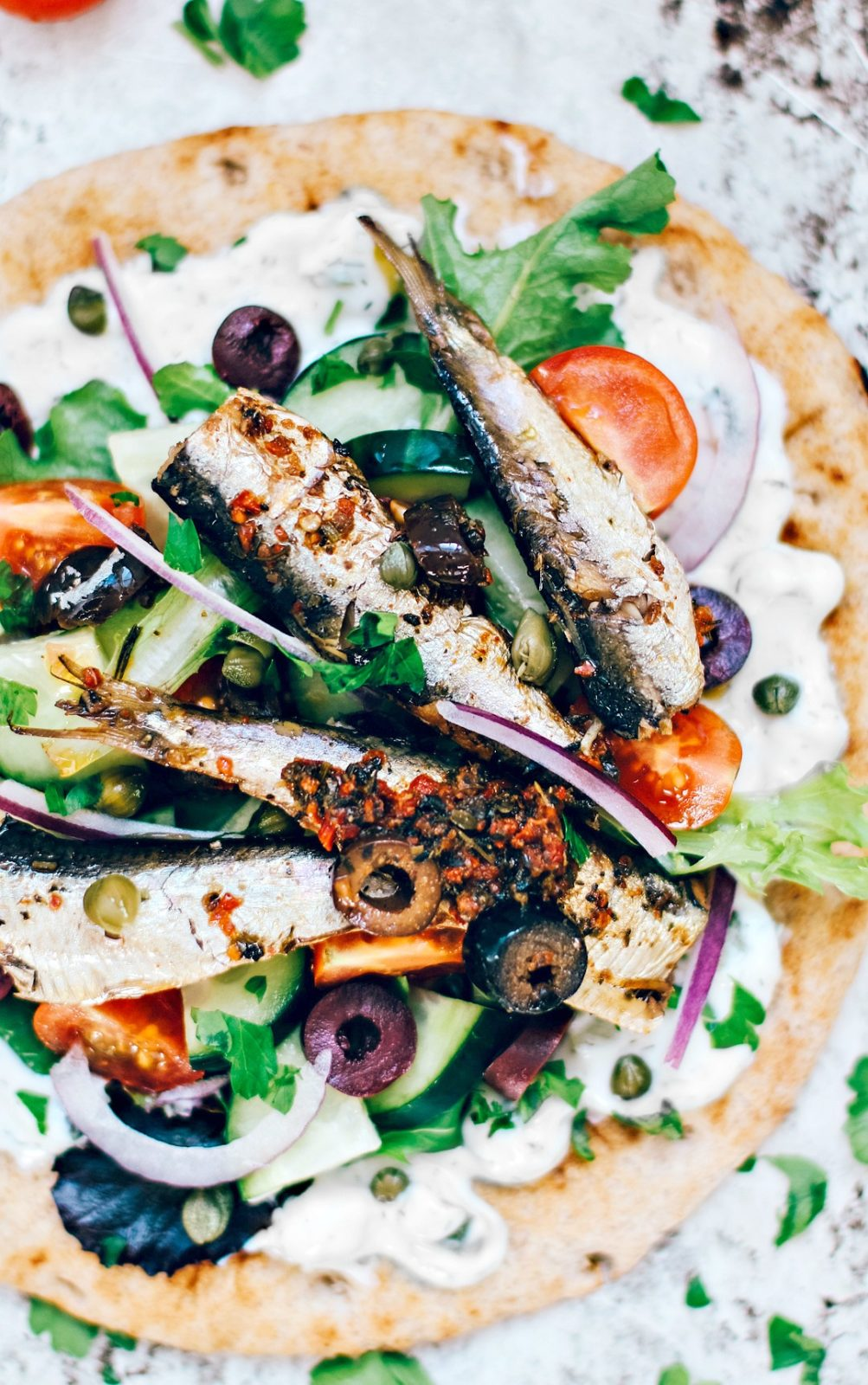 Pita topped with tzatziki, fresh veggies, and Mediterranean sardines.