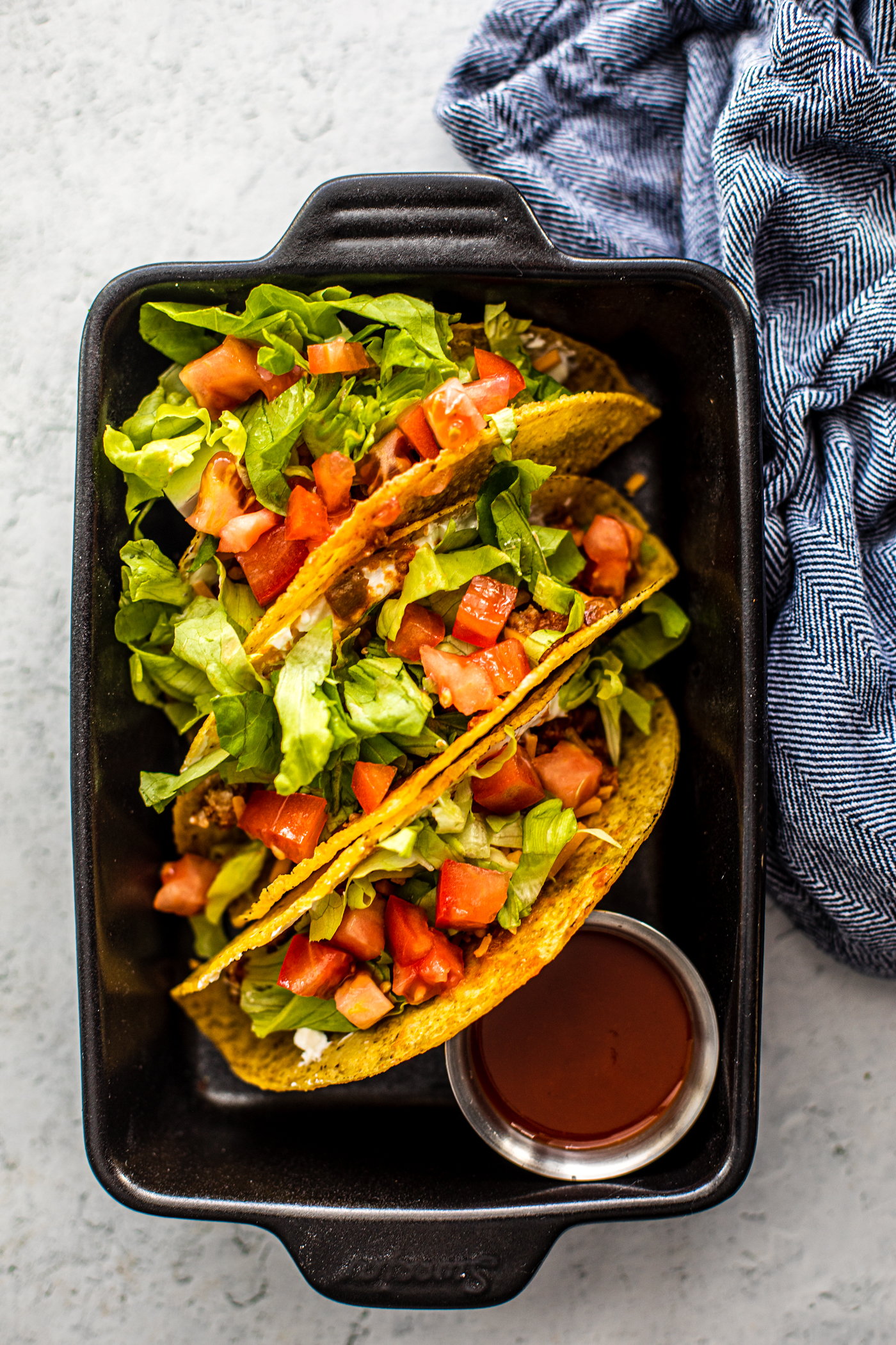 Small black cast iron pan holding tacos topped with tomatoes and lettuce.