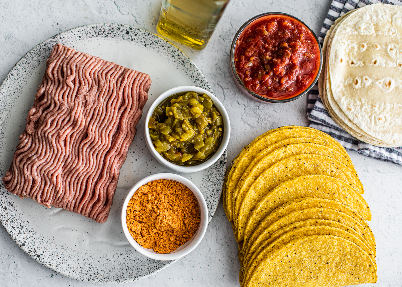 Ground turkey on a plate next to a pinch bowl of spices, canned chiles, salsa, hard shells and soft shells.