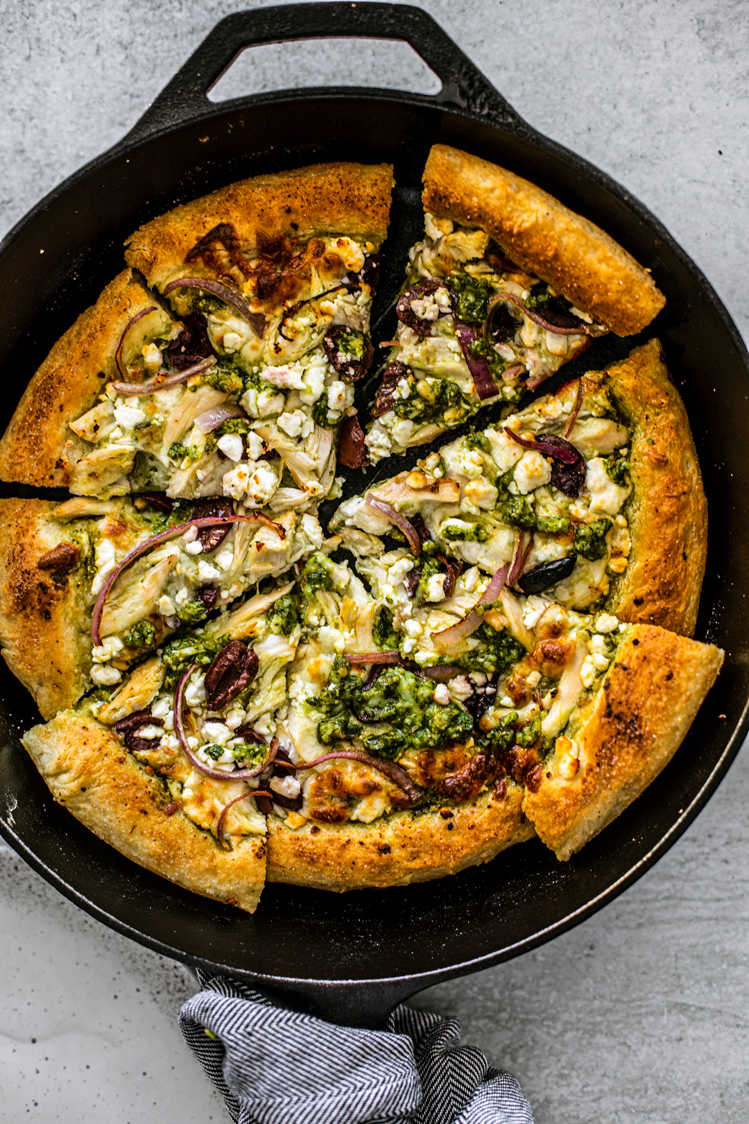 Skillet with chicken pesto pizza cut into slices.