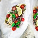 Flounder fillets sitting on parchment paper topped with bright ingredients.