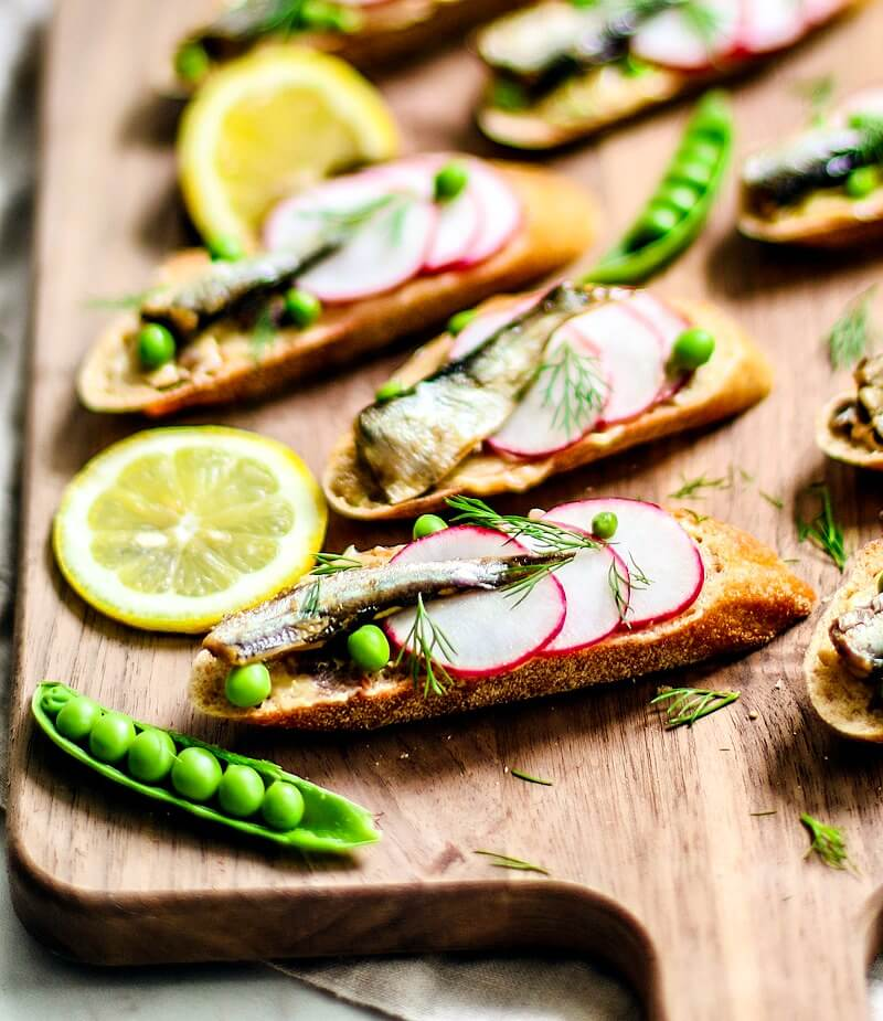 Close up of colorful canapés topped with radishes, peas, sardines, and dill.