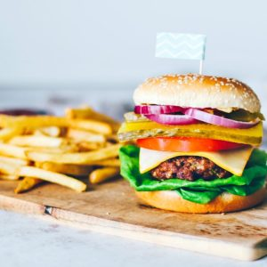 Stacked beef burger on a platter with fries.