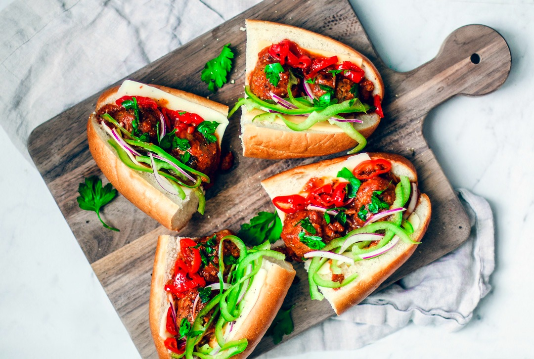 Loaded meatball sub sandwiches on a serving platter.