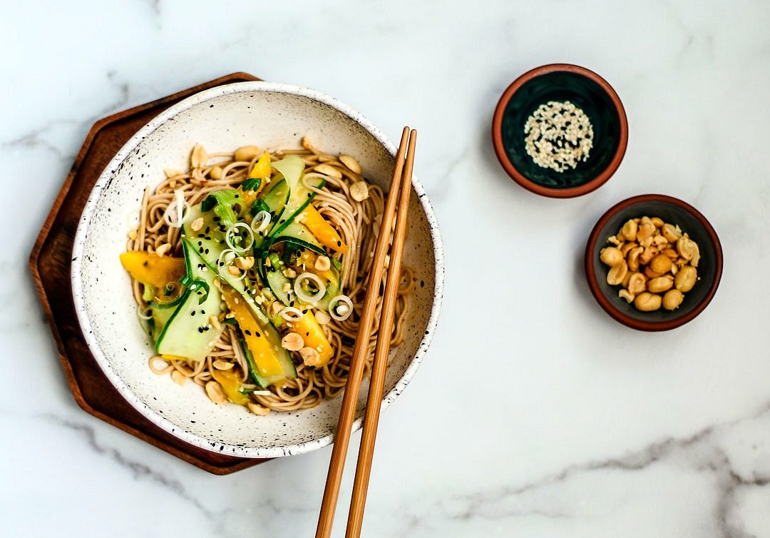 Bowl of sesame noodles with cucumber and mango salad.