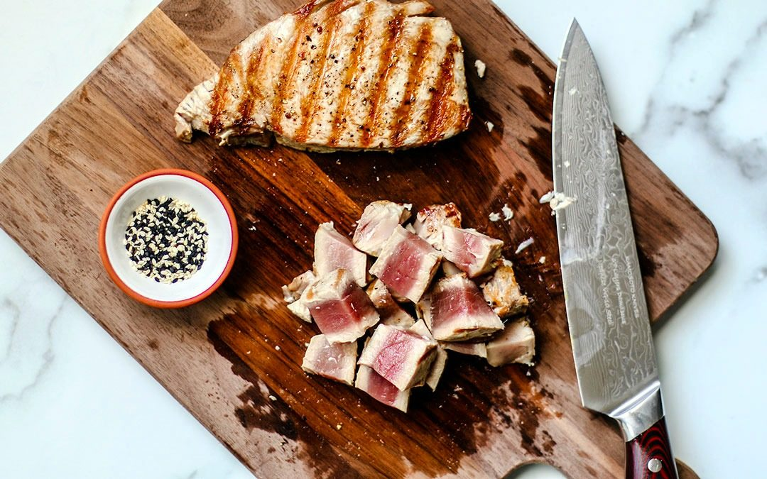 Cutting board with grilled tuna steaks on it.