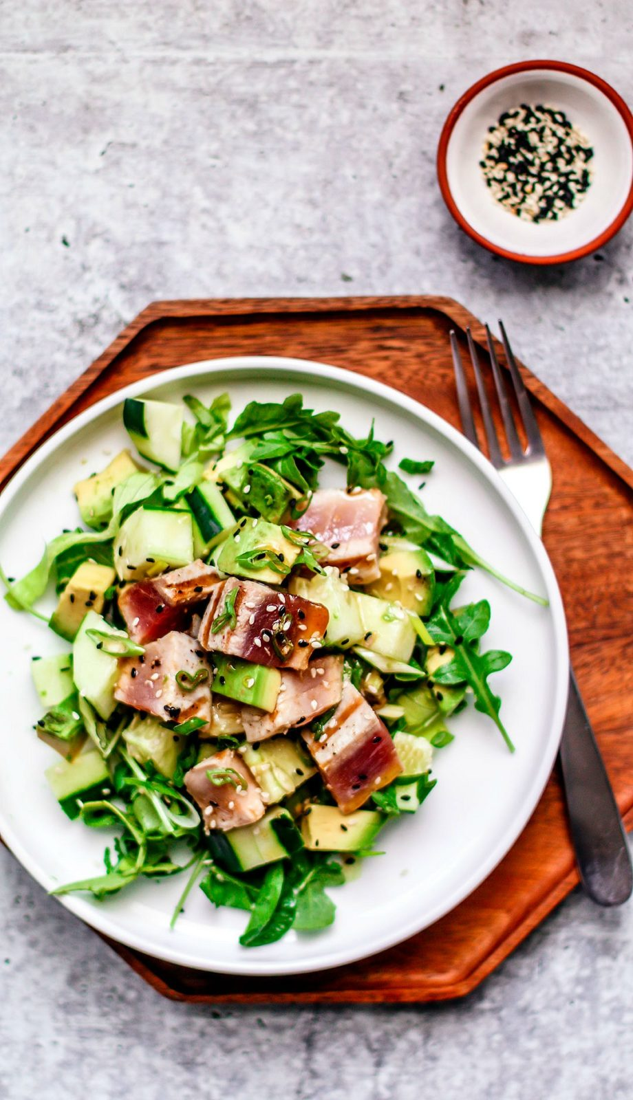 Plate of salad with grilled tuna on top.