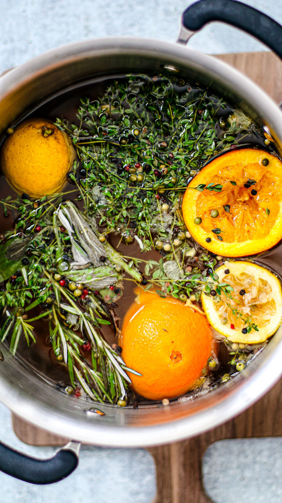 Stock pot full of turkey brine, fresh herbs, and citrus fruits.
