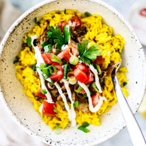 Bowl of golden rice, mackerel, tomatoes, and scallions.