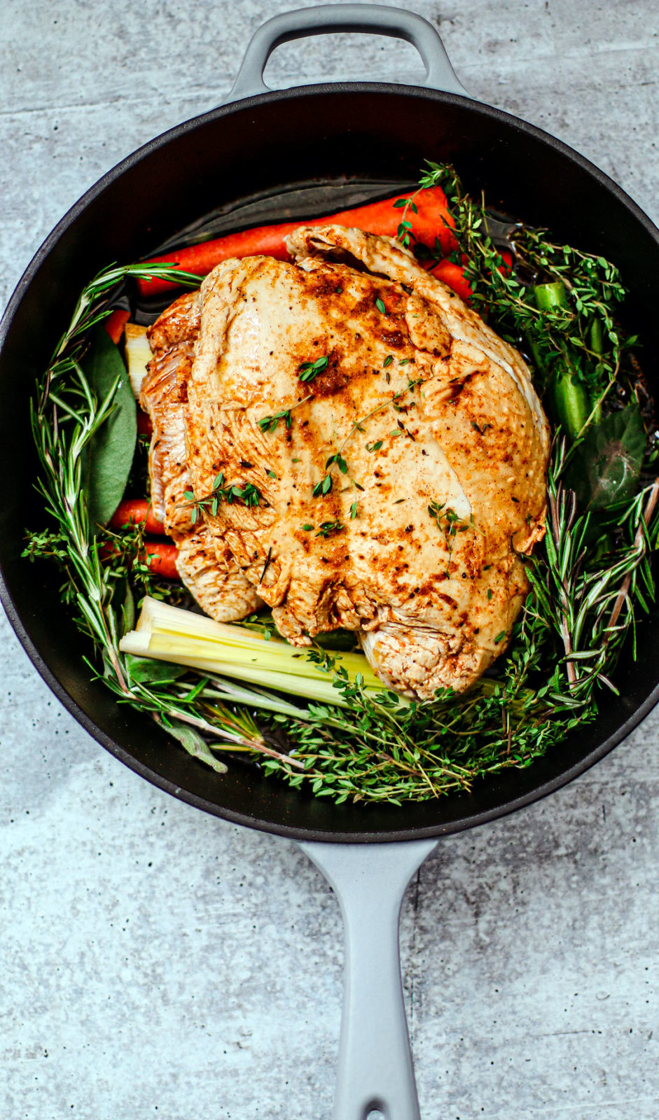 Turkey in pan with fresh herbs and veggies