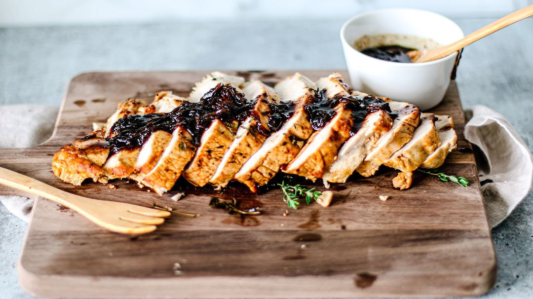 Roast turkey sliced on a wooden cutting board with cranberry glaze on top.