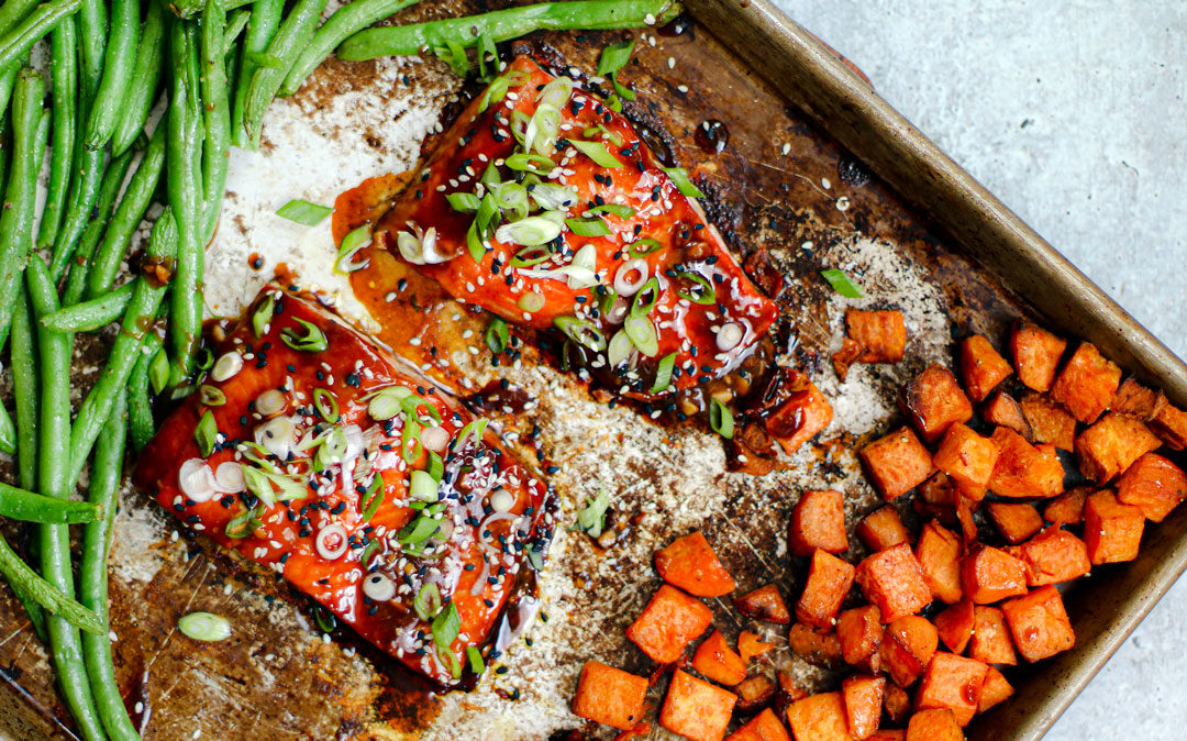 Two fillets of salmon on a sheet pan with veggies.