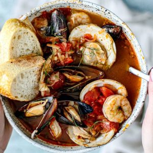 Hands holding bowl of cioppino.