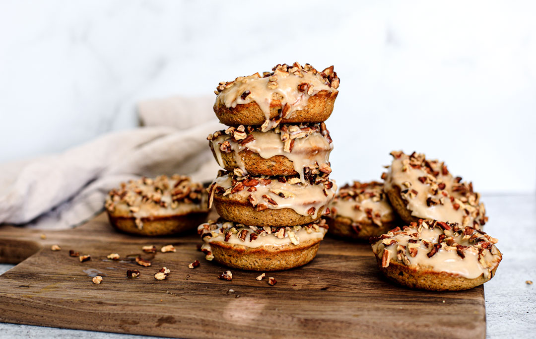 Stack of iced donuts sprinkled with toasted pecans.