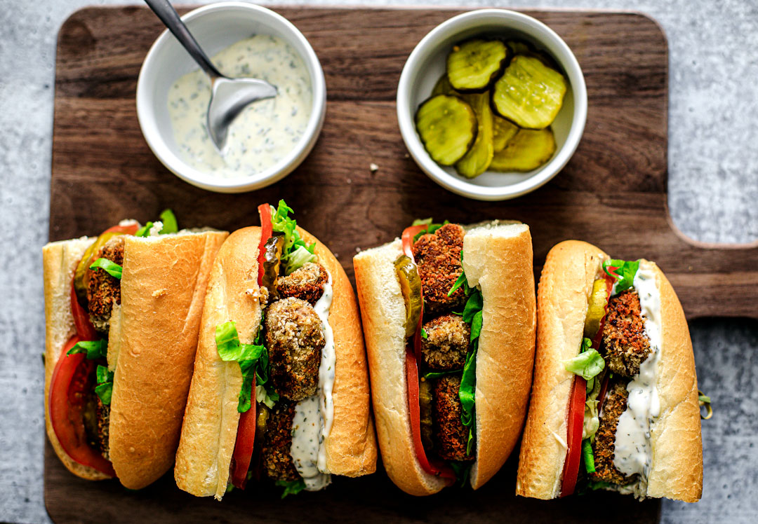 Cripsy Fish Po'boy Sandwiches lined up on a cutting board with a side of mayo and pickles.