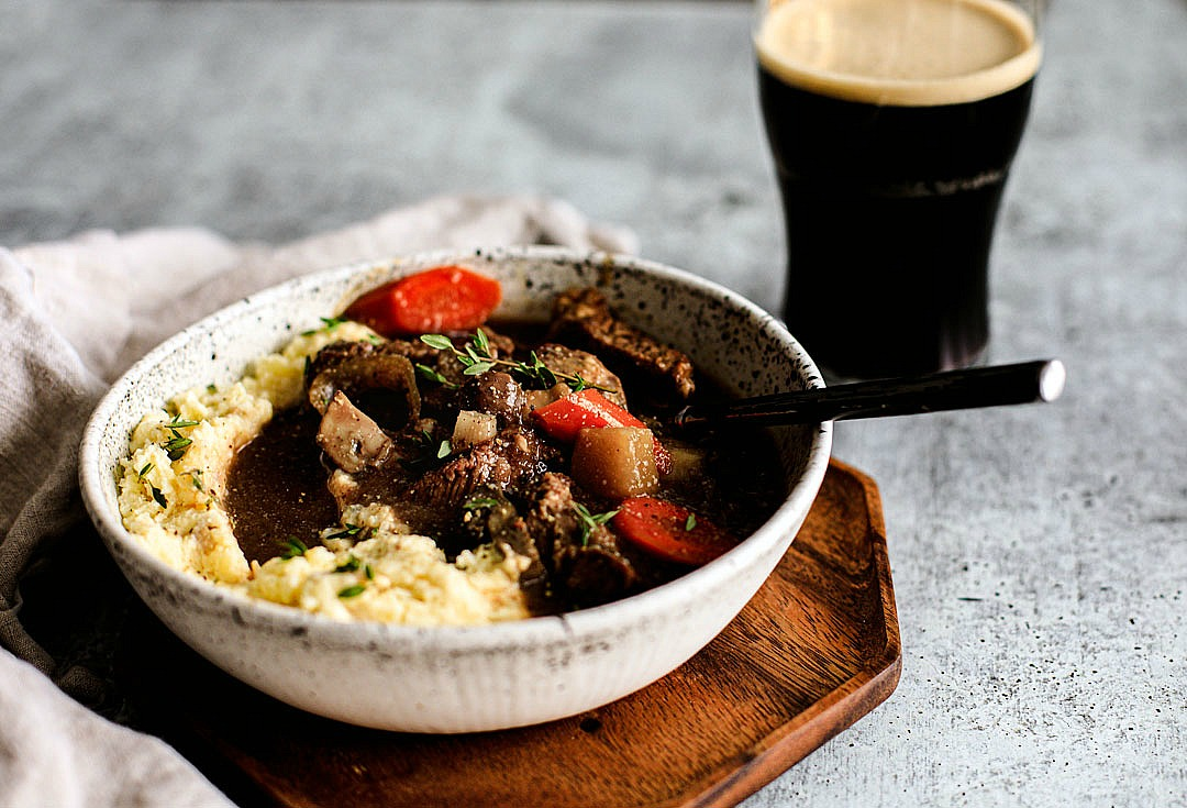 Close up of bowl of Guinness beef stew with a pint of Guinness.