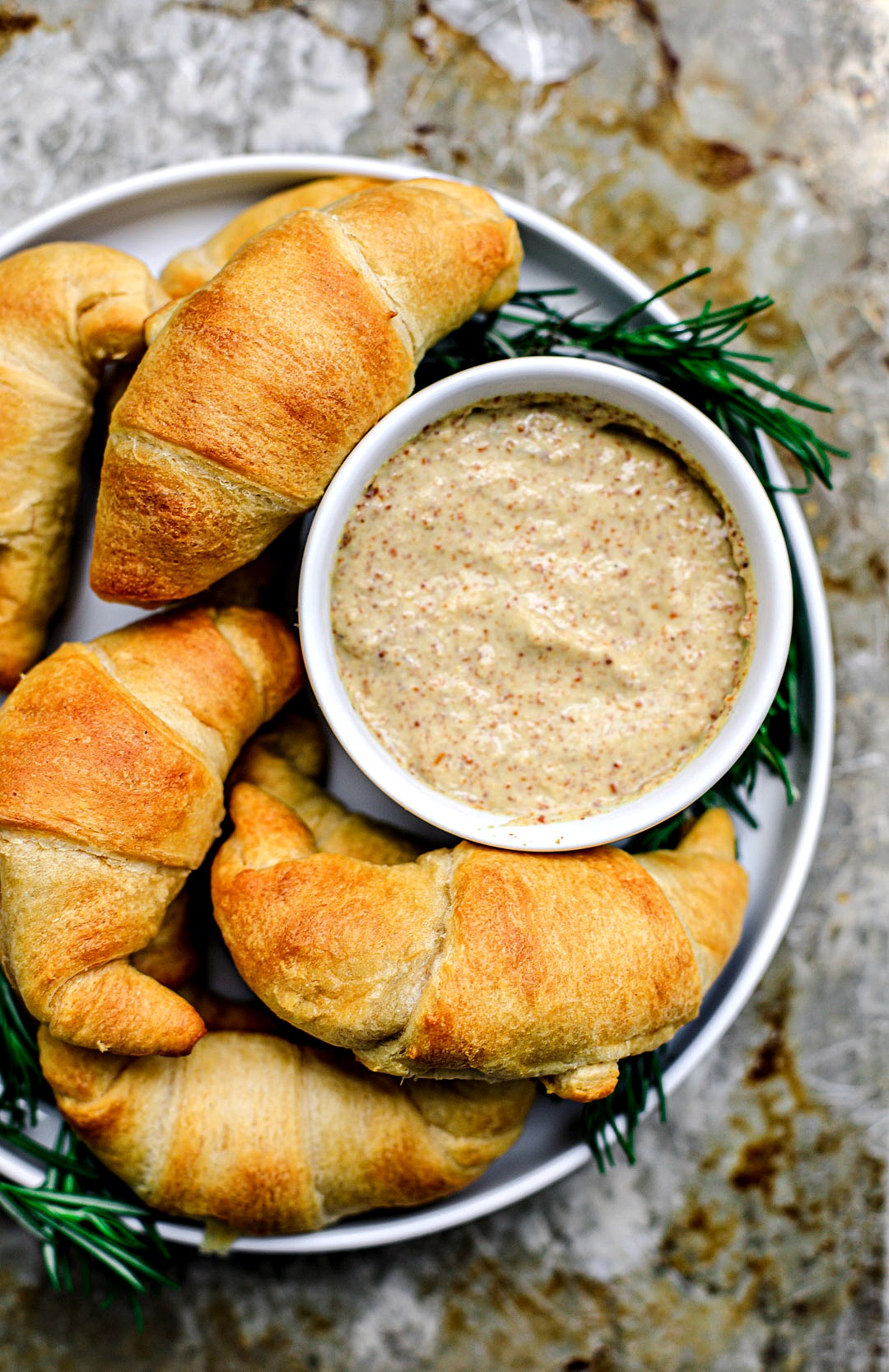 Close up shot of cheesy crescent rolls on a plate with stone ground mustard for dipping.