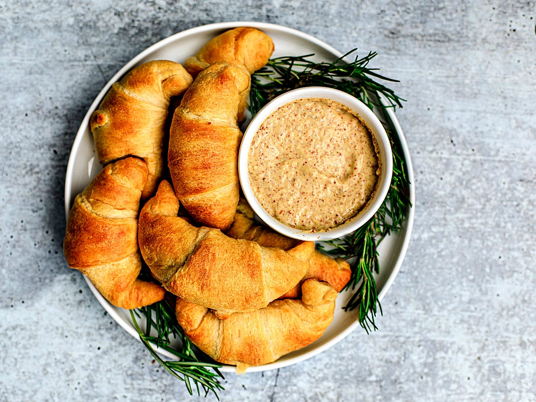 Festive plate of cheesy crescent rolls with small dish of stone ground mustard on the side for dipping.