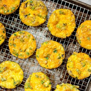 Cheesy egg muffins on a cooling rack.