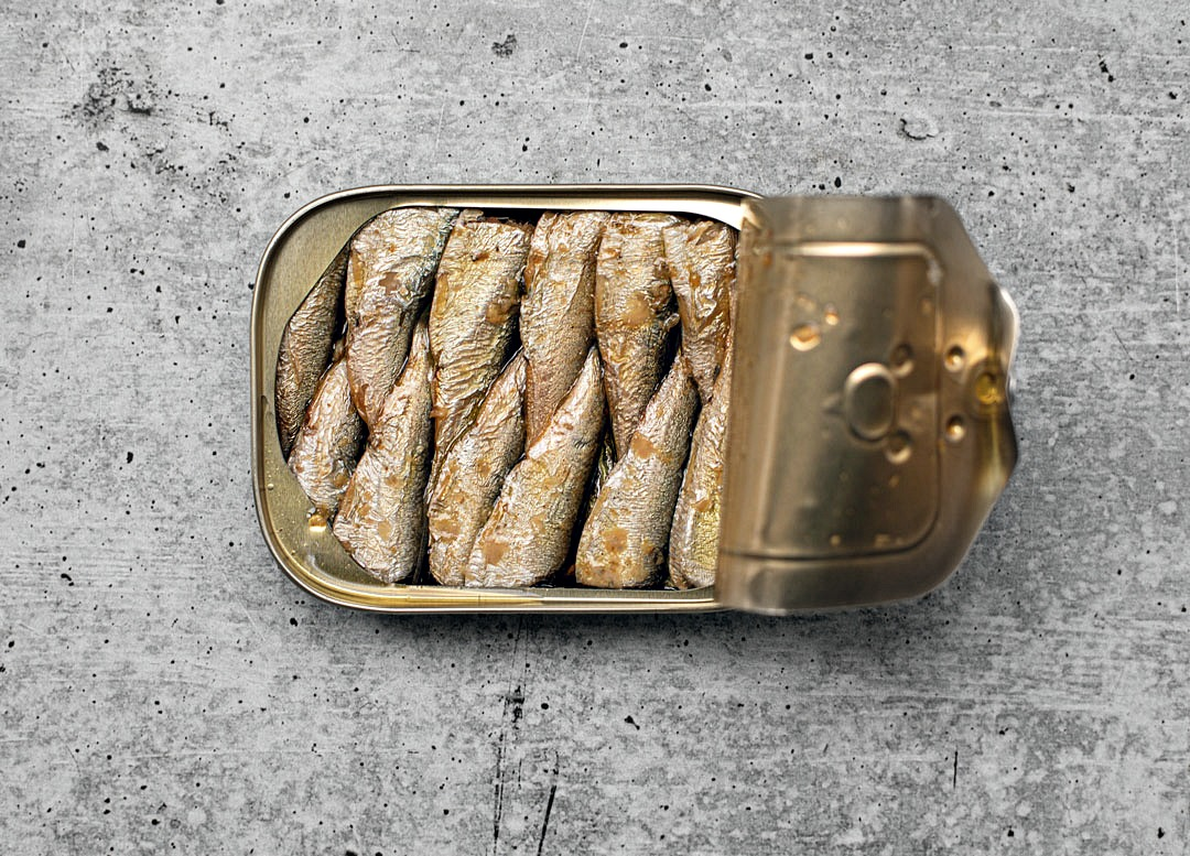 Opened can of King Oscar sardines exposing cross-packed fillets.