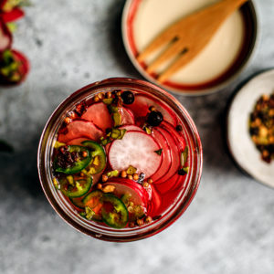 Close up of jar of pickled radishes with spices in the background.