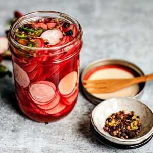 Side shot of jar of quick pickled radishes with pinch bowl of pickling spices.