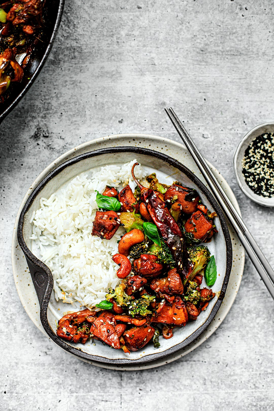 Plate of spicy sesame chicken with rice and chopsticks.