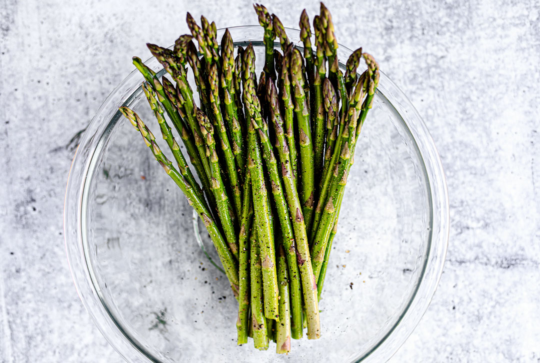 Seasoned asparagus in a glass bowl.