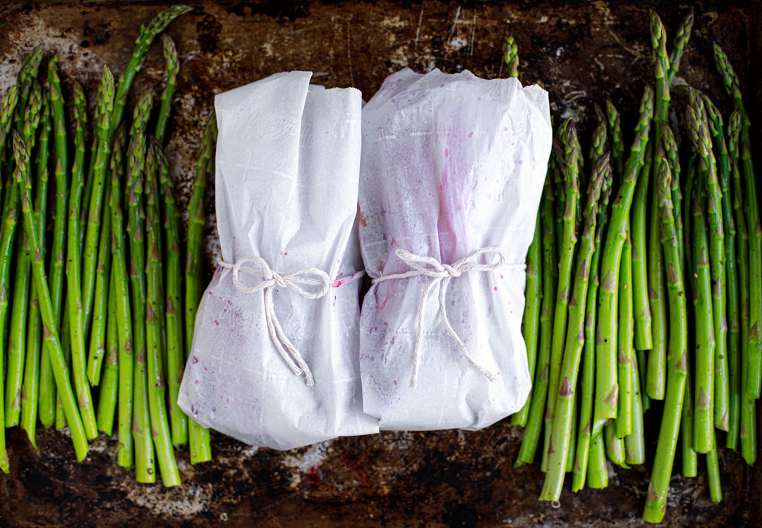 Parchment packets tied up with butcher's twine on a baking sheet with asparagus.
