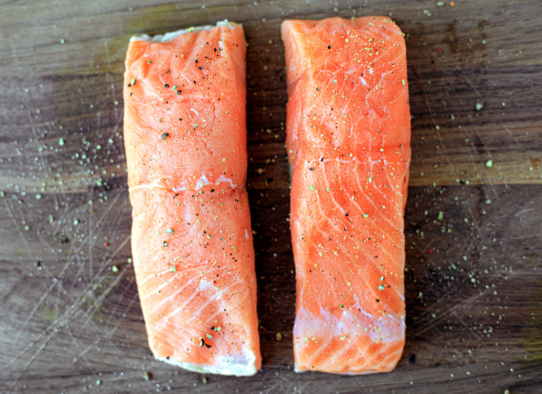 Two bright orange fillets of salmon seasoned with salt and pepper on a cutting board.