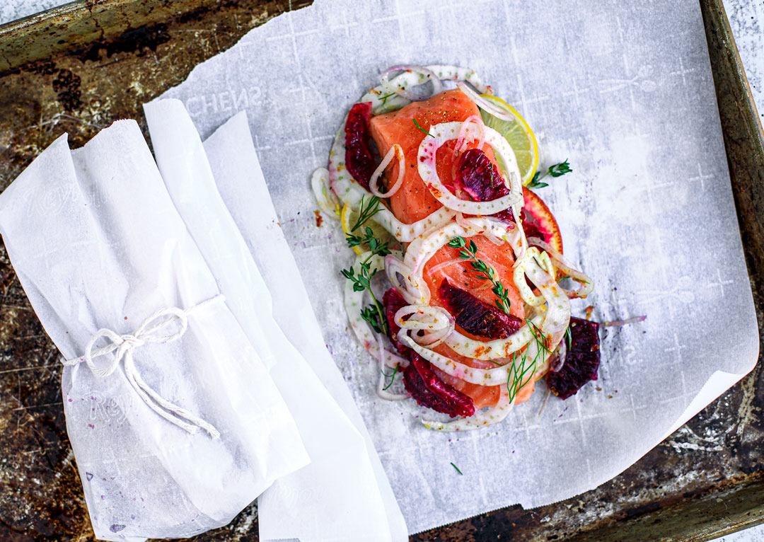 A fillet of salmon set in parchment paper with blood oranges and fennel on top.