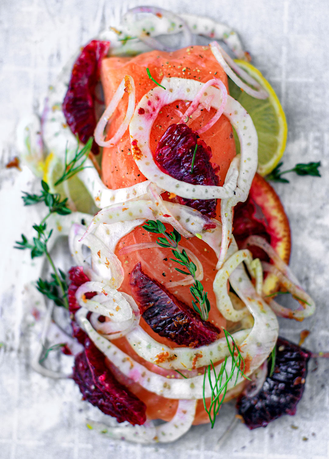 Uncooked salmon on parchment paper topped with a colorful salad of blood oranges and fennel.