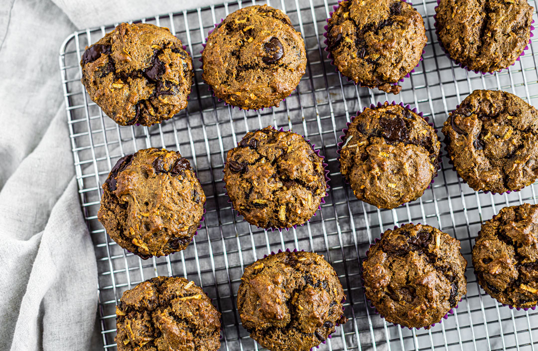 Cooling rack full of whole wheat chocolate chip muffins.