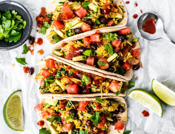 Loaded breakfast tacos full of scrambled eggs and veggies drizzled with hot sauce.