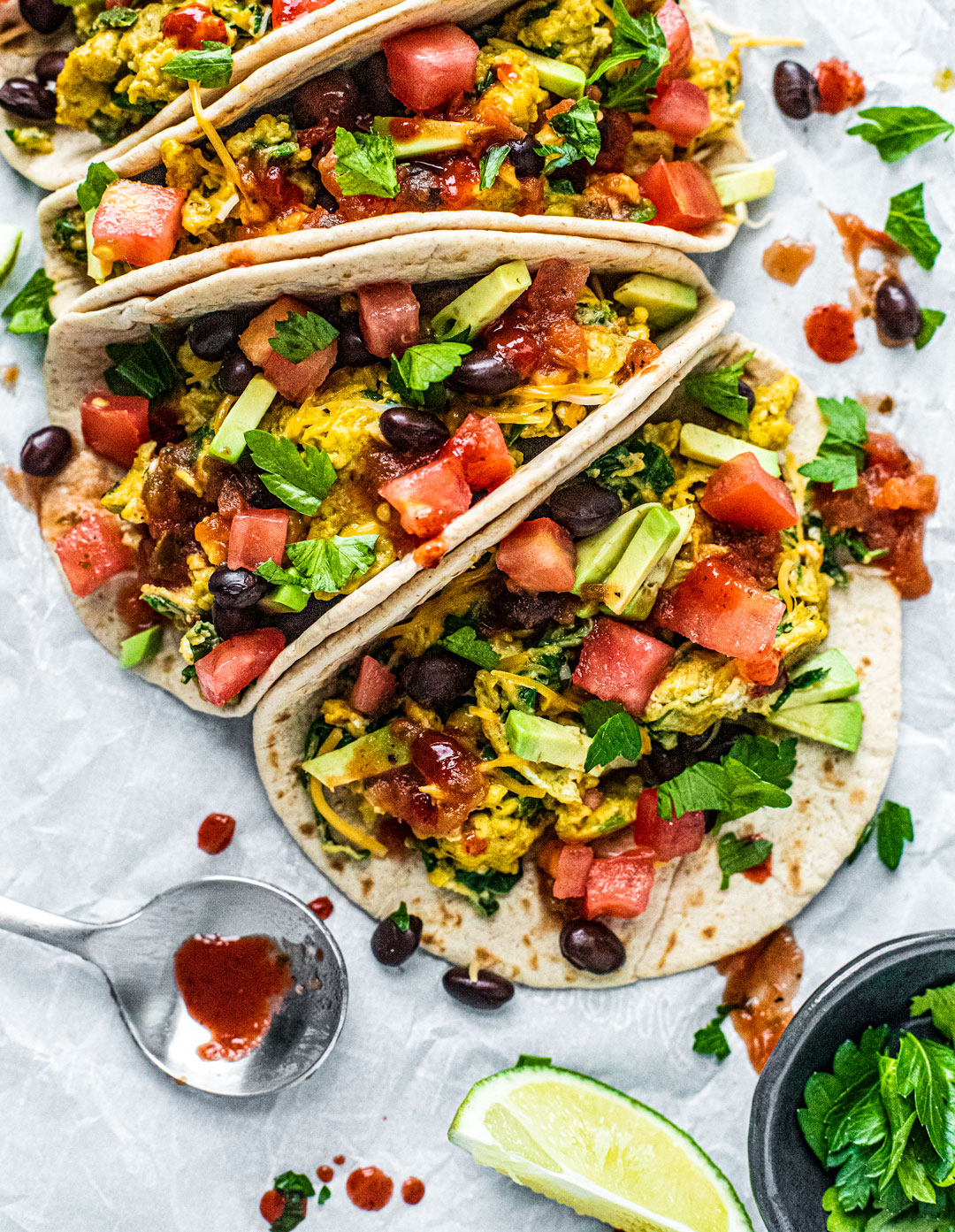 Platter of breakfast tacos stuffed with scrambled eggs, black beans, tomatoes, and drizzled with hot sauce.