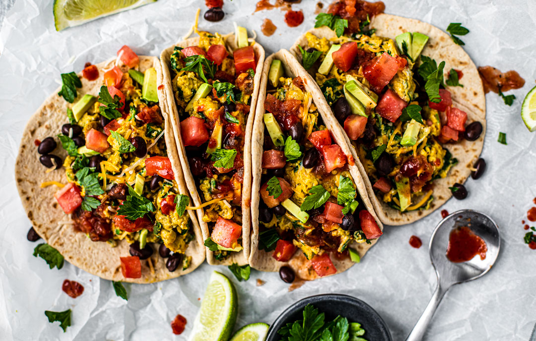 Loaded breakfast tacos drizzled with hot sauce and garnished with fresh herbs.